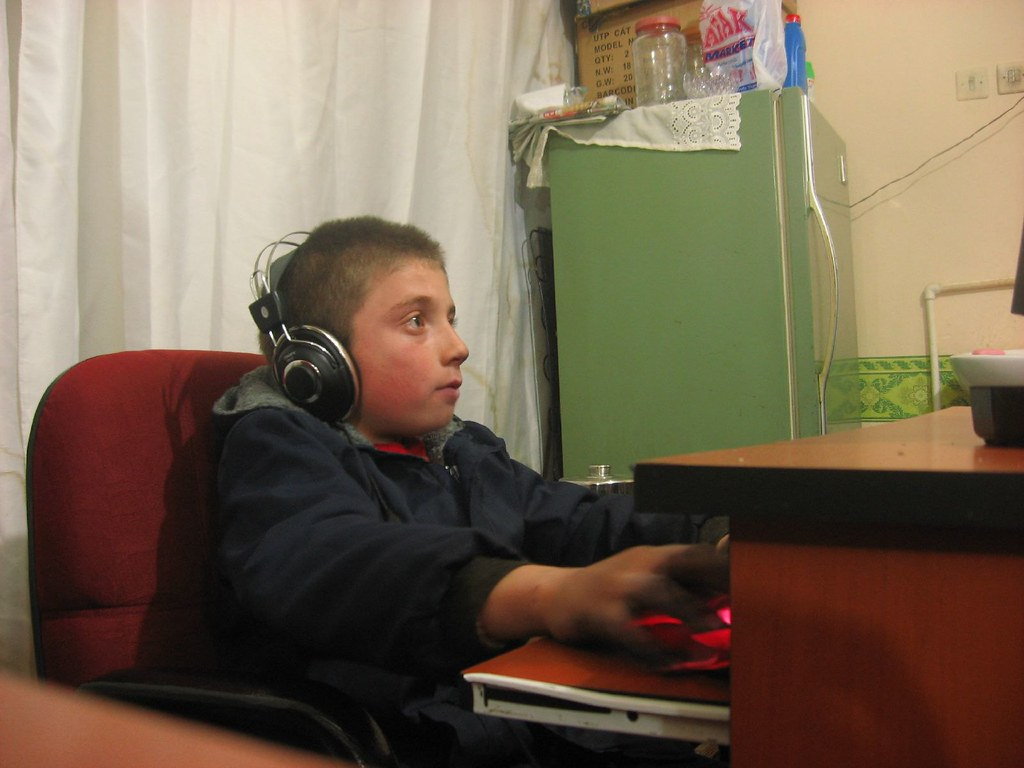 Kid in Turkish internet cafe absorbed in computer game (Tercan, Turkey)