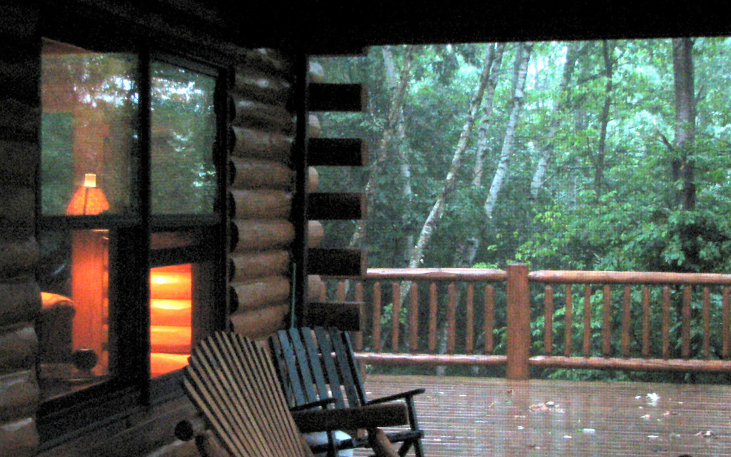 Cabin Porch In A Summer Rainstorm A Light Inside The