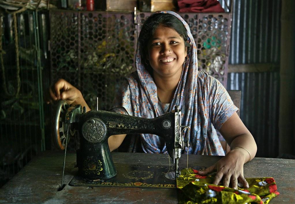 """缝纫活儿对孟加拉女性来说多半并不陌生,但从乡村到城市,同样踩着裁缝车,意义却大不同。(摄影:<a href=""""https://www.flickr.com/photos/michaelfoleyphotography/392624055/in/photolist-ccxG8d-AGisg-aB9ZMW-eaK2P5-eaE1bP-6sojJJ-eaK2FC-eaK2Rb-oNr66w-BFCgbm-BaqoKX-ALpWKo-BgNiQ7-BADn7H-BaquhP"""">Michael Foley/Flickr</a>)"""