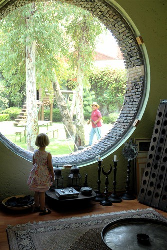 Pauline looking out of round window | by moline