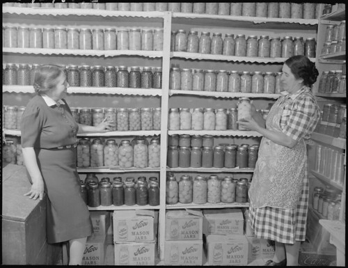 New Mexico. Mrs. Fidel Romero Proudly Exhibits Her Canned Food. [Two Women Standing in a Kitchen Pantry. Pantry Contains Preserved Fruits and Vegatables.] 1946 | by The U.S. National Archives
