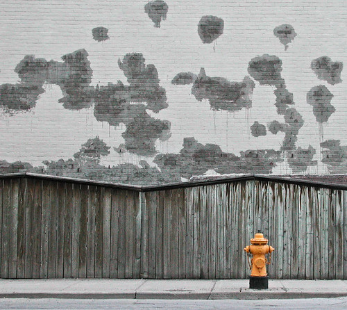 Hydrant against grey wall | by Kevin Steele