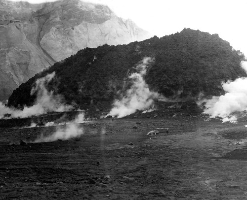 Black and white image shows a steaming mound of jagged lava on the crater floor.