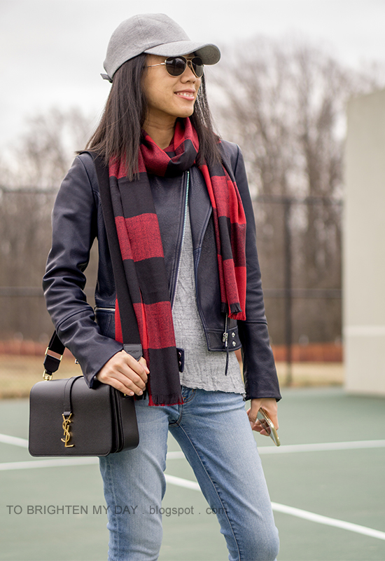 gray baseball cap, red buffalo check scarf, black leather jacket, gray tee, lightwash jeans black shoulder bag