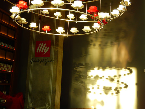 A chandelier made of coffee cups shines a spiral shadow on the wall of a Vancouver cafe