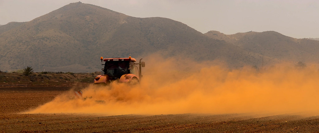 Tractor in dusty field