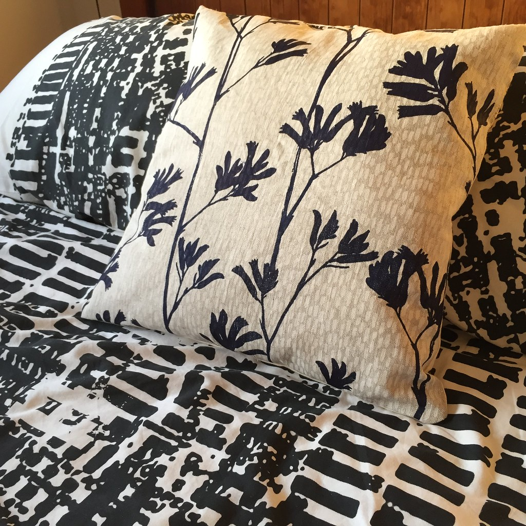 cushion made with ink and spindle fabric panel featuring navy blue kangaroo paws screen printed onto an oatmeal coloured linen