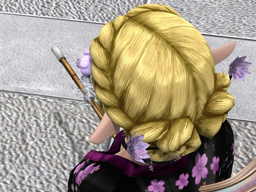 Image Description: Rear view down over a woman's head; her hair is pinned up with lotus flower hairsticks and she is staring at the point of her shinai.