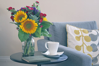 sunflowers and succulent flower bouquet on table next to sofa and pillow | by FTD Florists