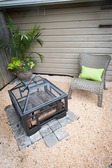 Overhead view of the firepit which sits on square 6x6 pavers on top of pea gravel and one of the outdoor chairs to the right and a beautiful mixed flower palm garden in a pot
