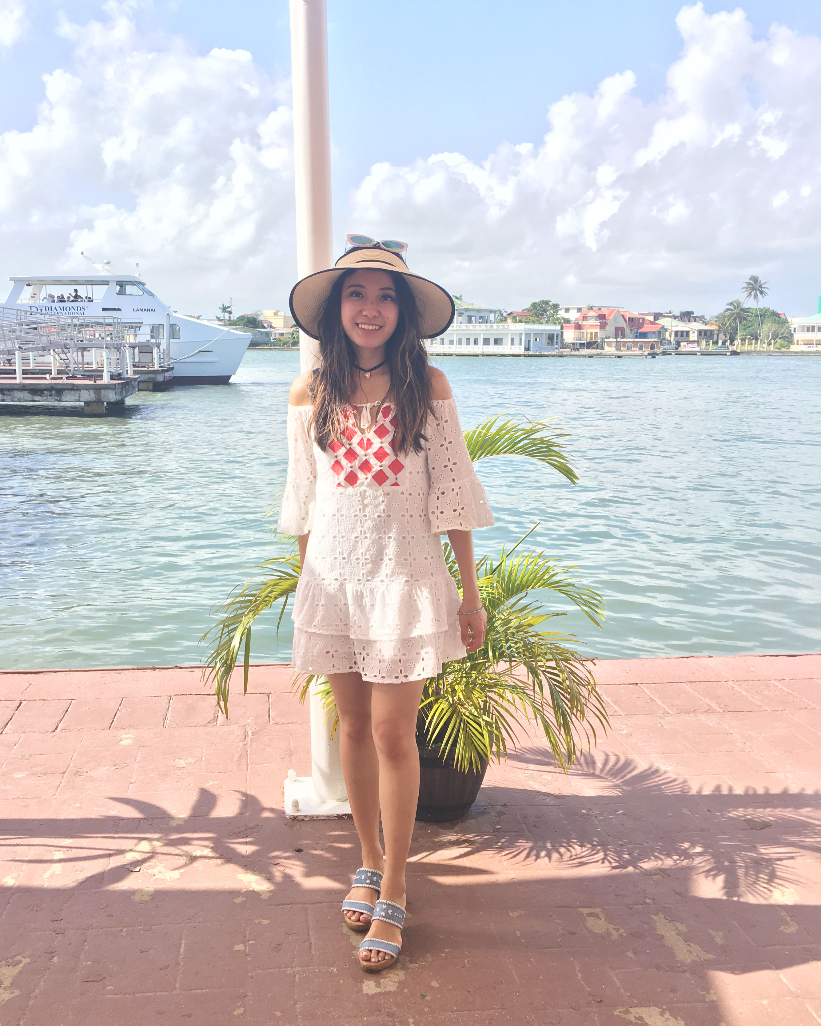 White off the shoulder dress and straw hat in Belize bay