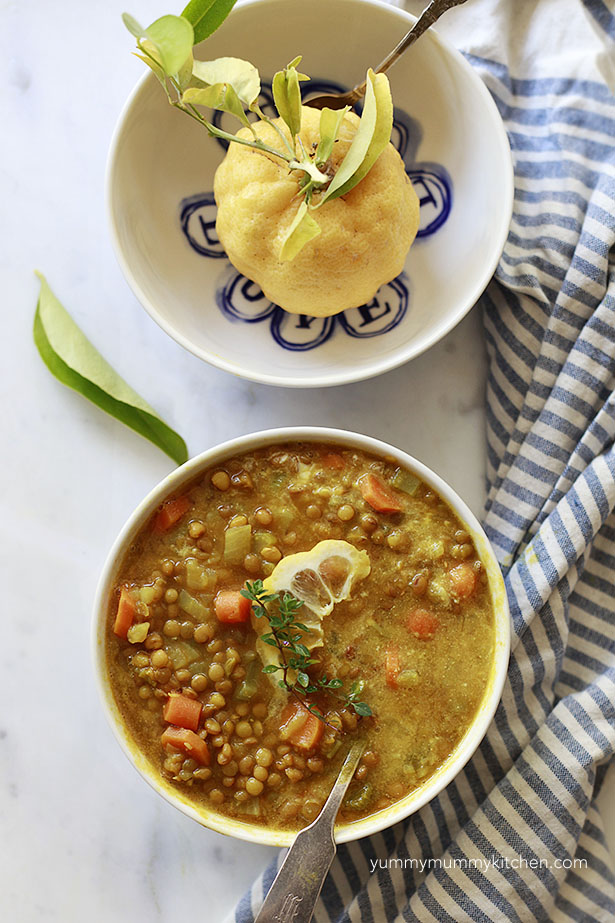 Lemony lentil soup in a bowl with a lemon and blue and white dish towel.