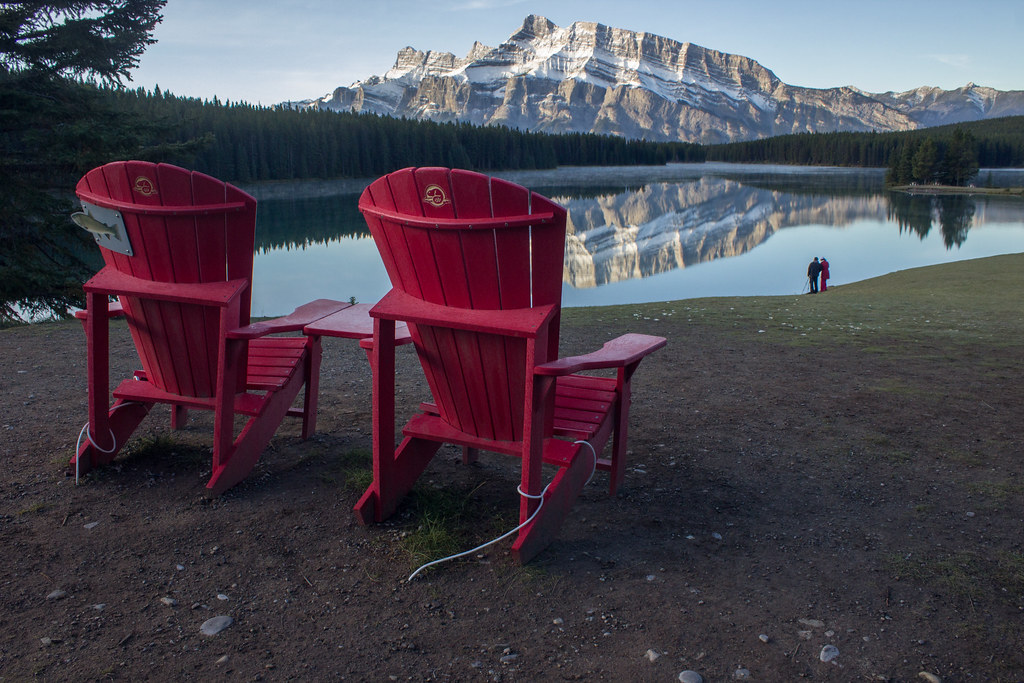 Two red chairs at Two Jack Lake, by Mount Rundle, Banff