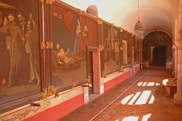 Interior of the former San Franciscan convent with its coral-coloured walls and huge paintings telling the story of the Virgin of Guadalupe in Guadalupe, Mexico