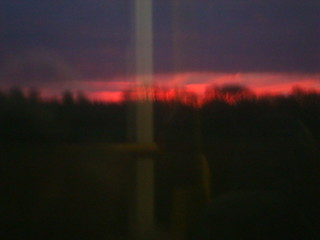 A red sunrise seen through a bus window