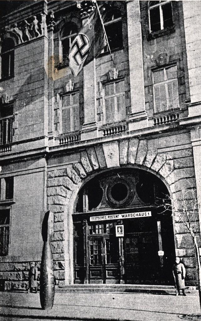 Poste de Varsovie gardée par des soldats avec la photo d'Hitler à l'entrée et le drapeau à la croix gammée flottant au-dessus.