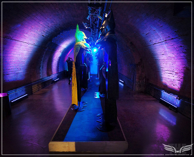 The Establishing Shot: BATMAN: ARKHAM KNIGHT CAPE & COWL EXHIBITION - L-R GOTHIC GOTHAM BY LOGAN HICKS & YELLOW BAT CAPE CLUB   BY JON BURGERMAN - KACHETTE, LONDON