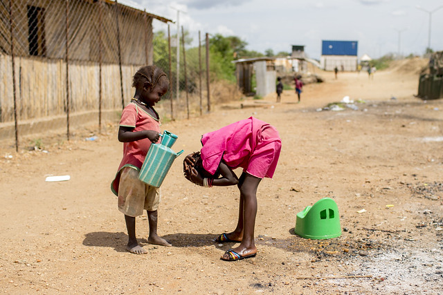 A little girl helps cool off her sister by pouring water over her head in Juba South Sudan.