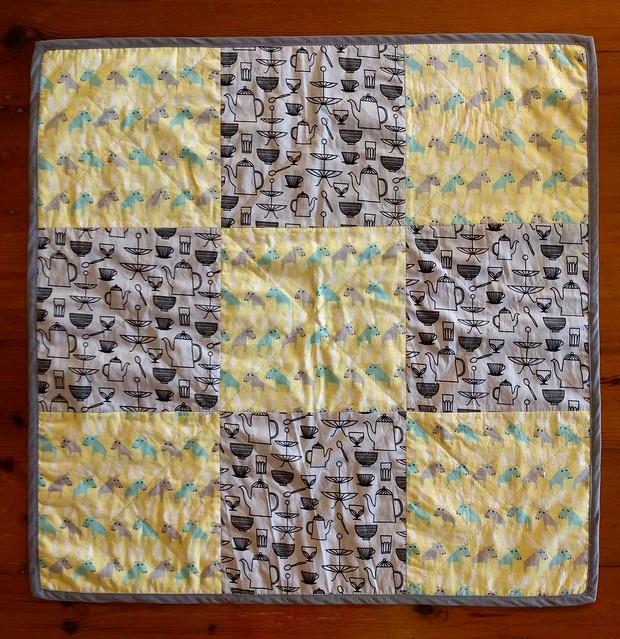 An image of a simple baby quilt. Made from even squares of two fabrics, one grey with cutlery print, another yellow with moose print.