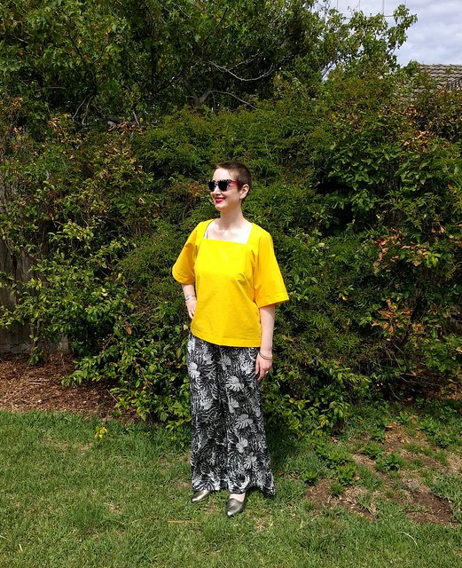 A woman stands in a garden, wearing a bright yellow, boxy top, sunglasses, and fern print palazzo pants.
