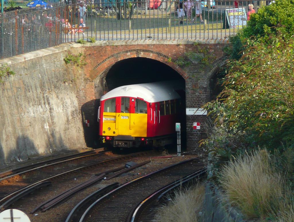 Traukinys įvažiuoja į tunelį ir išvažiuoja iš jo.