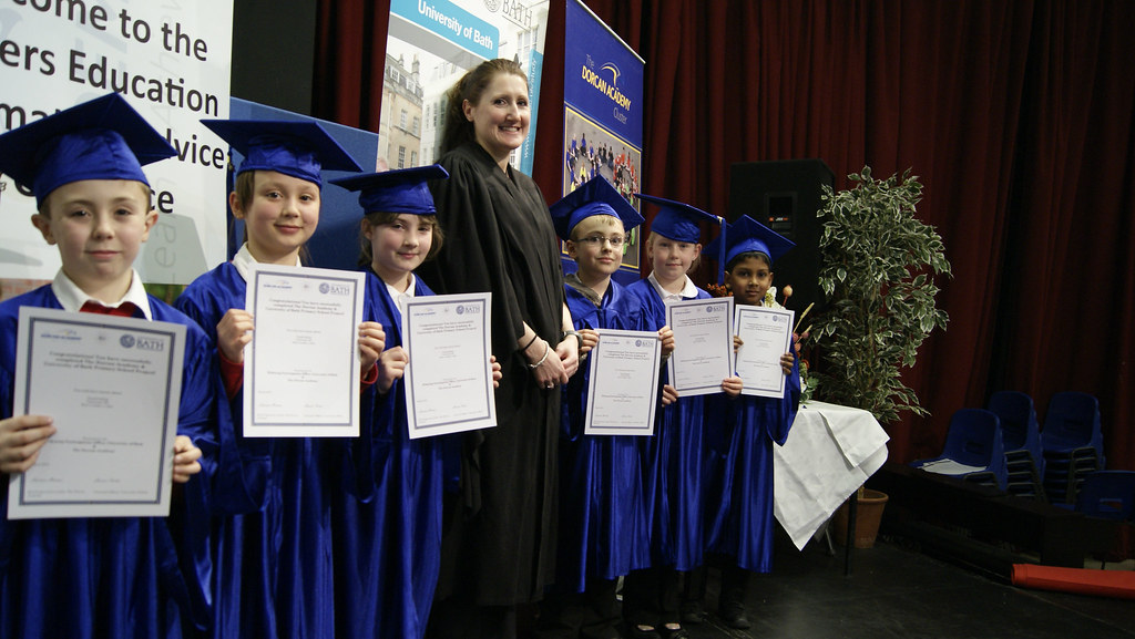 Primary school students and their teacher having their photo taken as part of a mock graduation ceremony