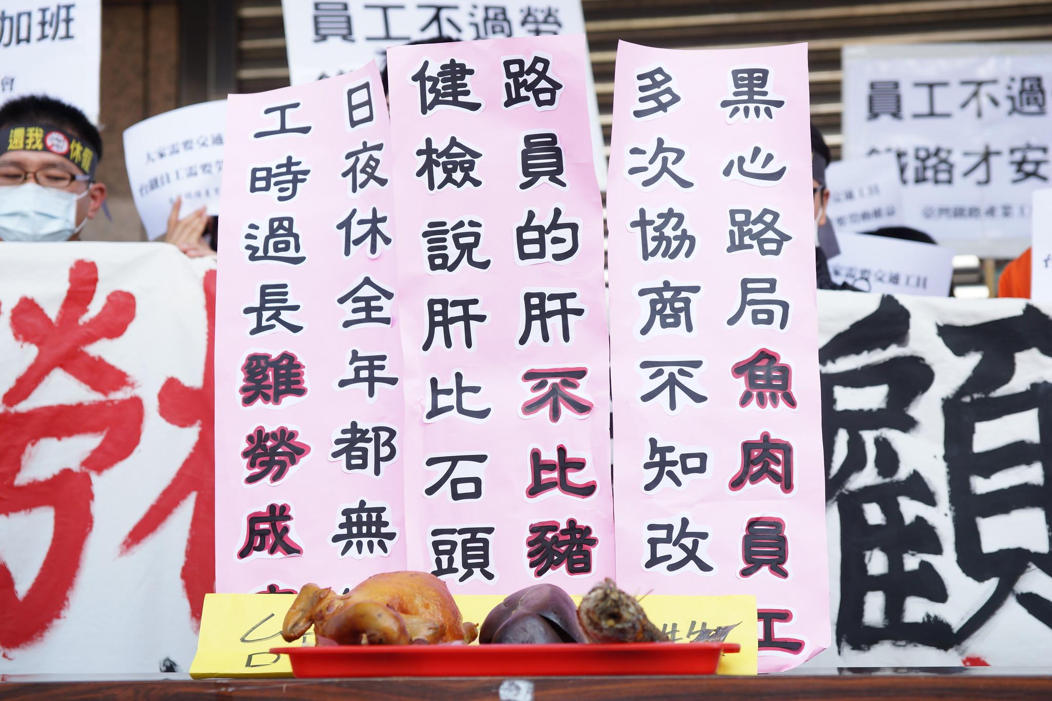 """工会祭出鸡、鱼、肝三牲,讽刺员工工时过长""""鸡劳成疾""""、路员的肝""""不比猪肝""""、黑心路局""""鱼肉员工""""。(摄影:王颢中)"""