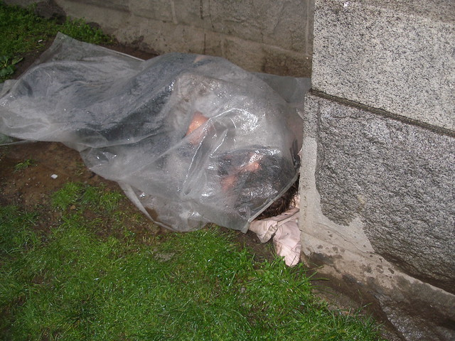 homeless man sleeps under rain-spattered plastic sheet