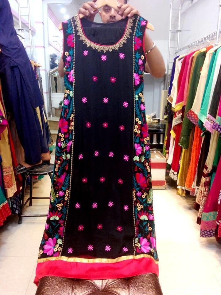 Shop owner in karachi showing a sindhi dress with kundi em