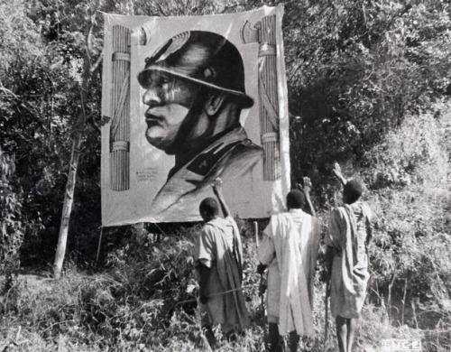 Three Ethiopian men saluting an image of Mussolini in Addis Ababa, Ethiopia, 1936