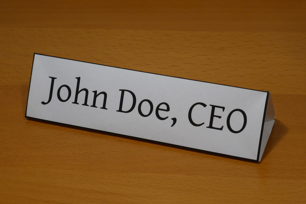 Do professional titles really tell us about the person or the job? A fake nameplate with John Doe, CEO.