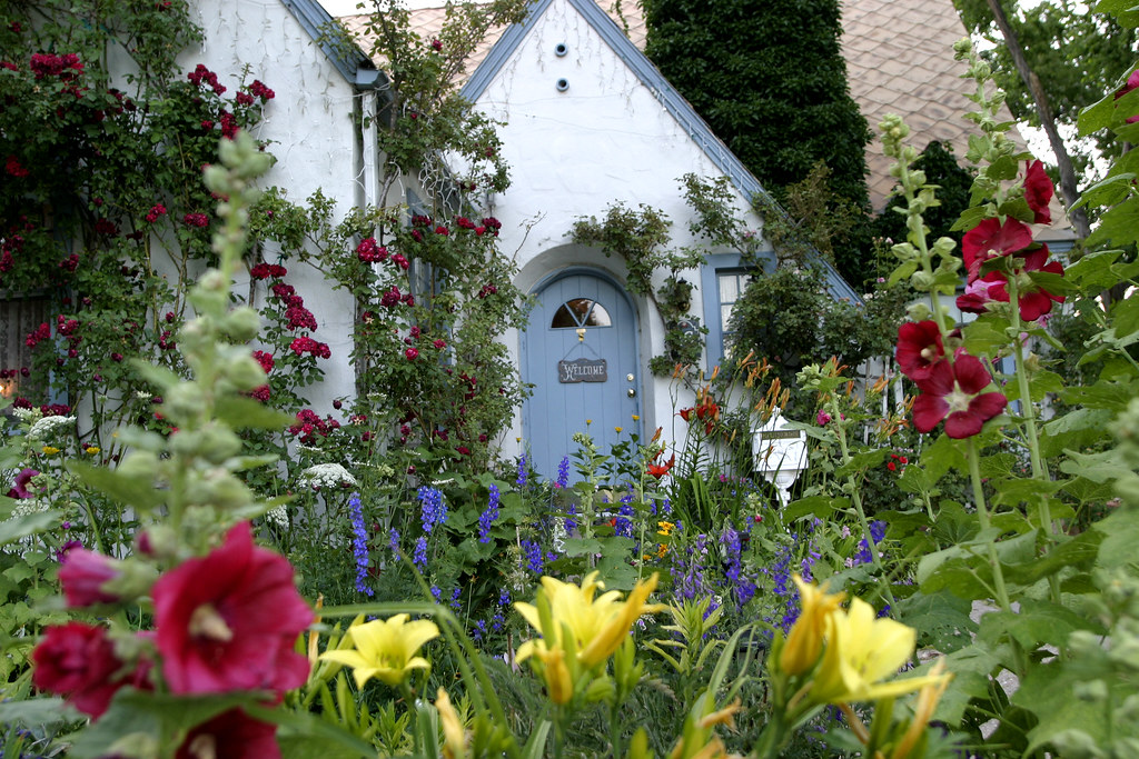 Cottage Nestled In The Garden Bountiful Blooms At The
