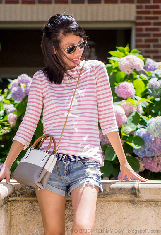pink striped top, navy striped belt, distressed shorts, colorblocked crossbody bag