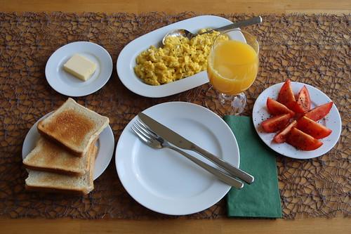 Frühstück mit Rührei, Toast und Tomate sowie Orangensaft