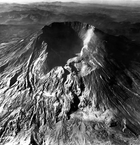 Black and white aerial image of Mount St. Helens, taken from nearly directly above the new crater. There is no lava dome yet, just a scooped-out interior and a huge gouge in the rim where the north face gave way.