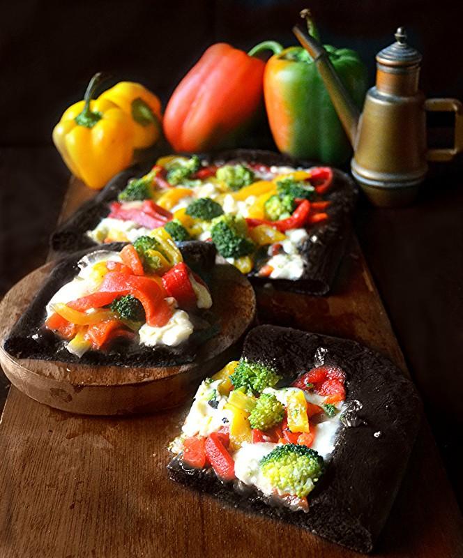 Pizza nera al carbone vegetale con peperoni e broccoli