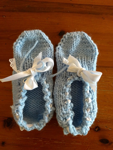 Handknit blue slippers with lace and ribbon trim.