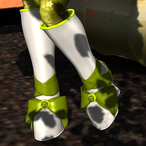 Image Description: Closeup of a pair of knee-high, gray boots with a large, green bow over the toes.