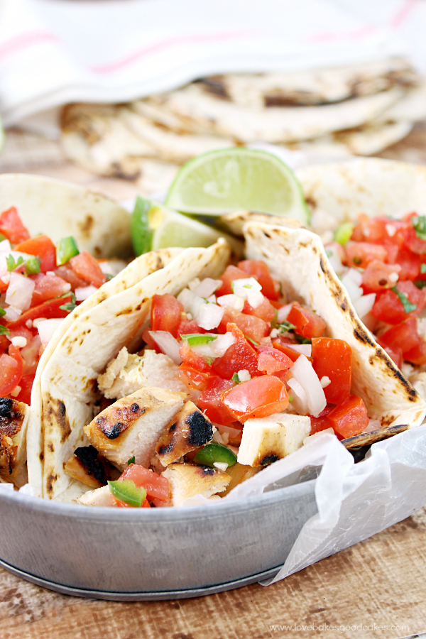 Grilled Chicken Fresco Tacos on a metal bowl with fresh limes close up.