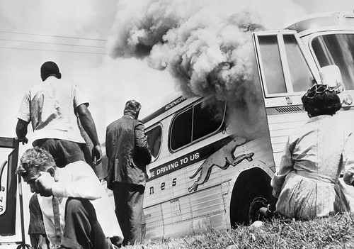 Members of the Freedom Riders and other passengers sit on the ground after their Greyhound bus was fire-bombed.