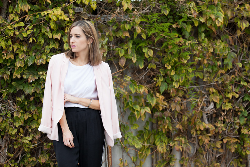 Pale pink blazer with a white t-shirt and black pants