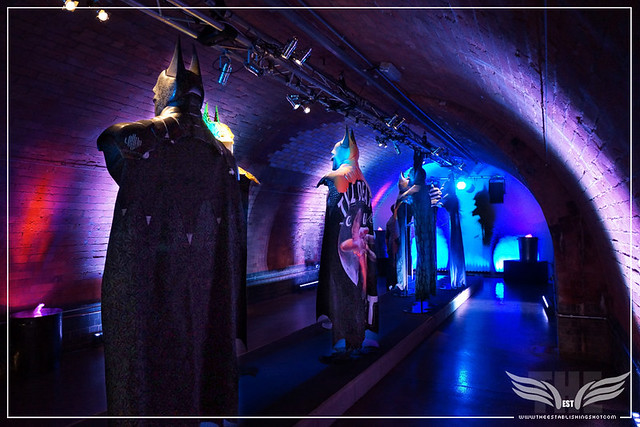 The Establishing Shot: BATMAN: ARKHAM KNIGHT CAPE & COWL EXHIBITION - L-R GOTHIC GOTHAM BY LOGAN HICKS, (HIDDEN) YELLOW BAT CAPE CLUB BY JON BURGERMAN & TILL DEATH DO US PART BY CASE - KACHETTE, LONDON