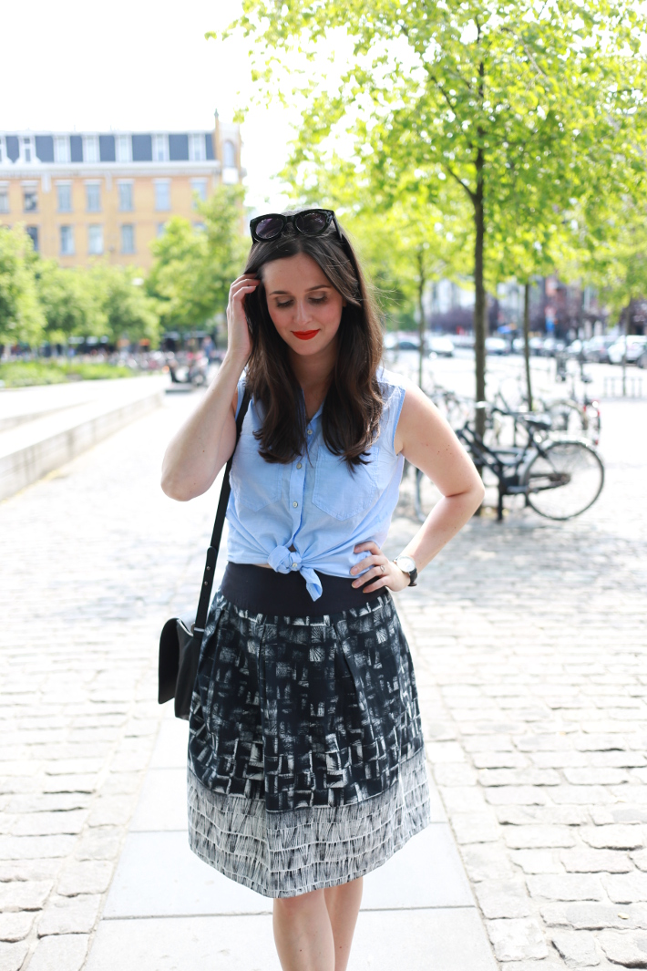 professional outfit: business casual in light blue shirt tied at the waist, abstract printed skirt