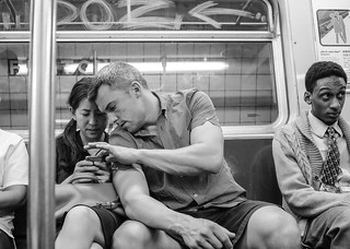 New York City Street Scenes - On the Subway - A Couple Checking Their Phone | by Steven Pisano