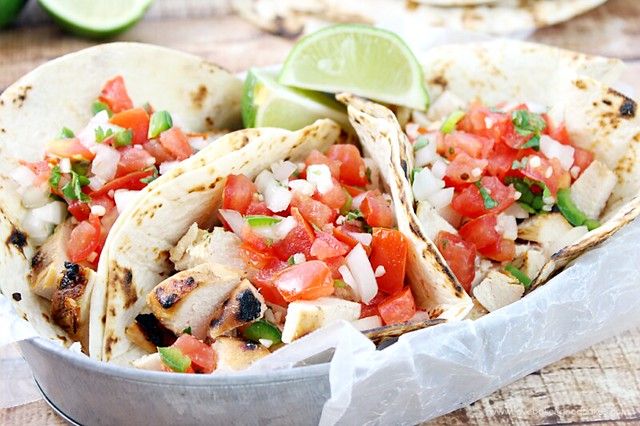 Grilled Chicken Fresco Tacos on a metal bowl with fresh limes close up from the side.