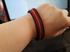 woven bead bracelet in reflected stripes of black, dark red, bright red and gold