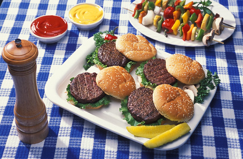 A plate of hamburgers beside vegetables on skewers, ketchup, mustard and a pepper shaker
