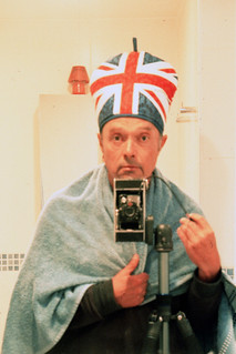 reflected self-portrait with Agfa Billy camera and union flag hat