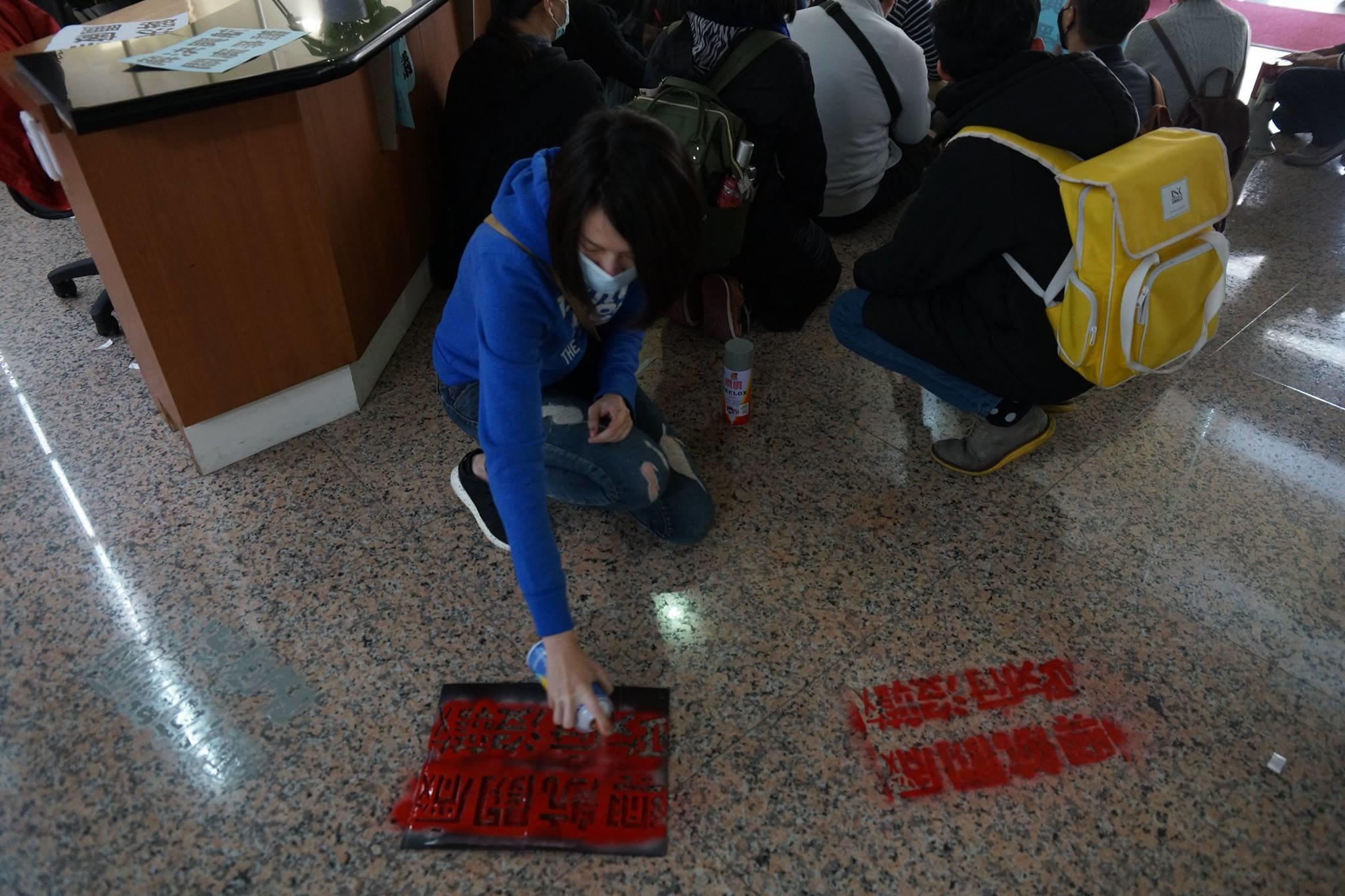 工會成員在勞動部地板上噴漆,表達訴求。(攝影:王顥中)