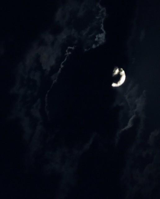 Moon behind storm clouds
